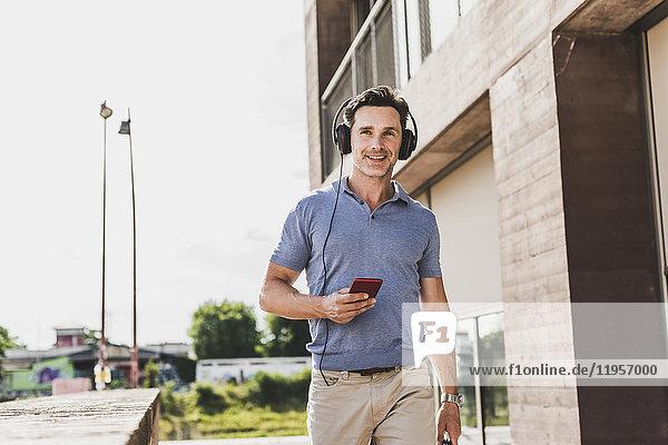 Geschäftsmann zu Fuß in der Stadt  mit Smartphone und Kopfhörer