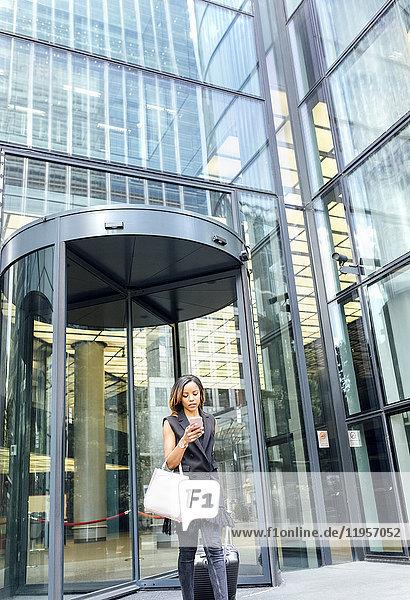 Geschäftsfrau verlässt ein Bürogebäude in der Stadt