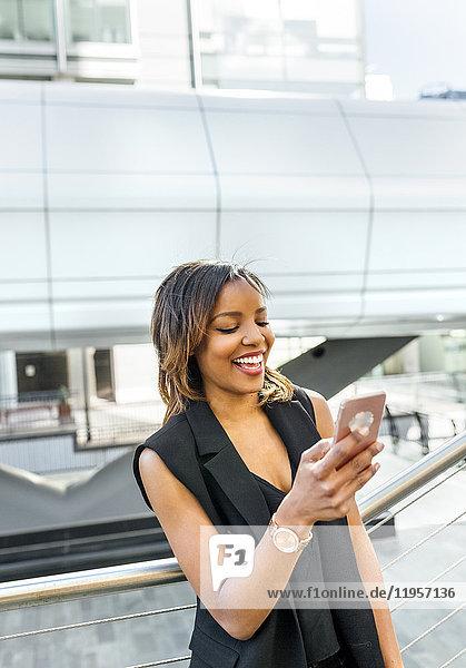 Lächelnde Frau schaut auf ihr Handy in der Stadt