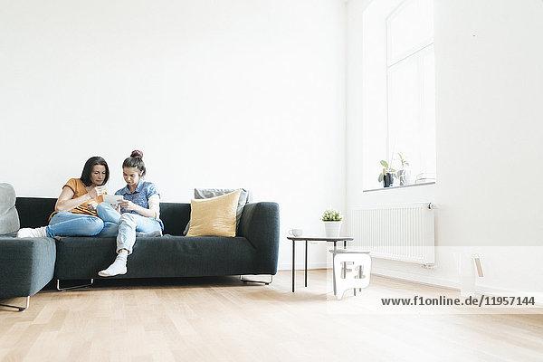 Zwei Frauen zu Hause sitzen auf der Couch und schauen sich Fotos an.