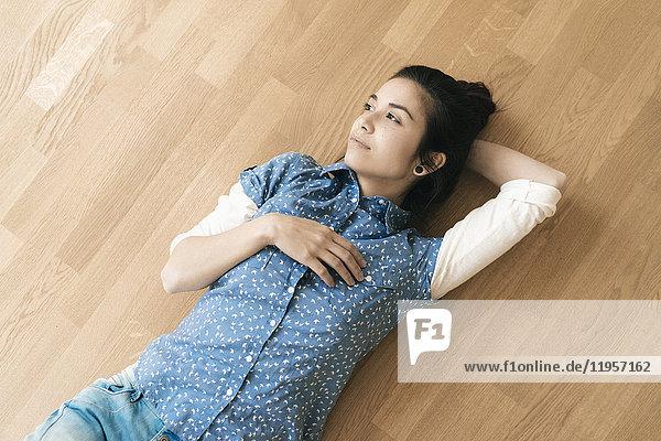 Frau auf Holzboden liegend