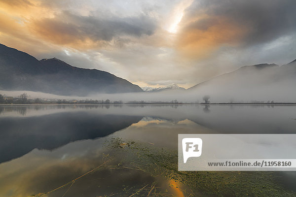 Mountains reflected in water at dawn shrouded by mist  Pozzo di Riva Novate  Mezzola  Chiavenna Valley  Lombardy  Italy  Europe