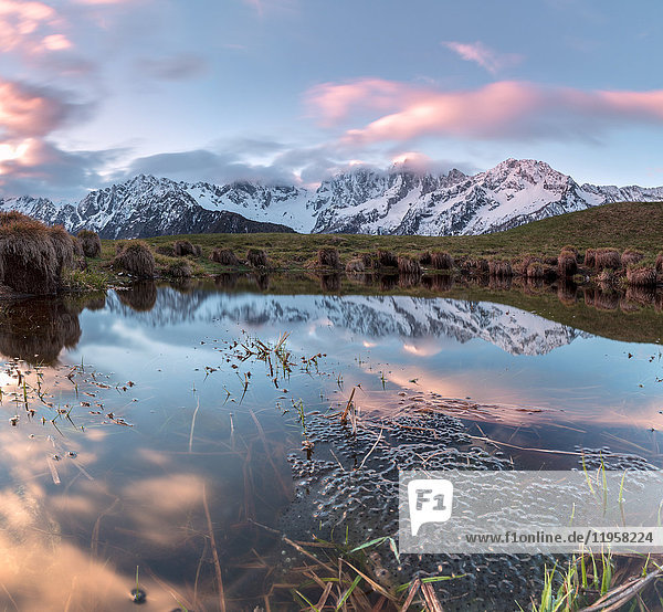 Panorama of pink clouds reflected in water at dawn  Tombal  Soglio  Bregaglia Valley  canton of Graubunden  Switzerland  Europe