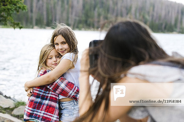 Mother taking pictures of son (6-7) and daughter (8-9) by lake