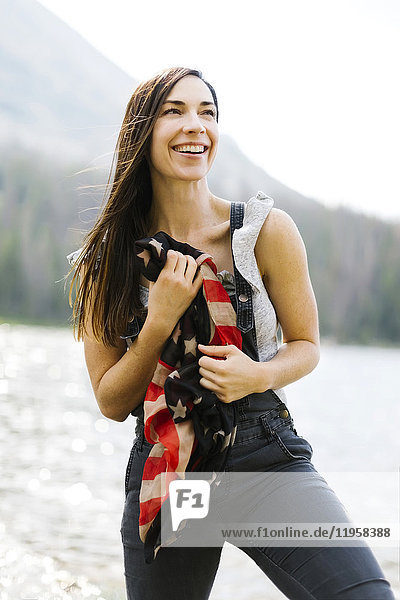 Portrait of woman holding us flag by lake