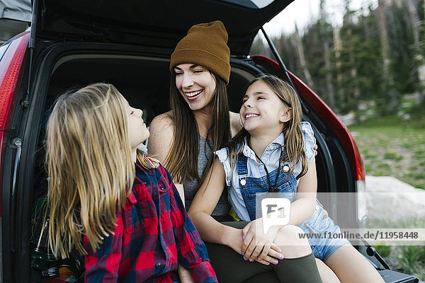 Woman with son (6-7) and daughter (8-9) in back of car