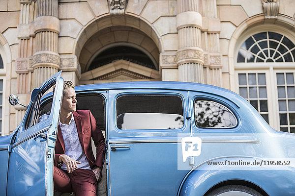 Elegant man sitting in vintage car