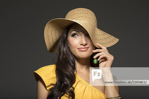 Portrait of woman wearing straw hat and yellow top
