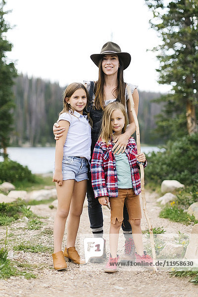 Outdoor portrait of mother with kids (6-7  8-9) in forest