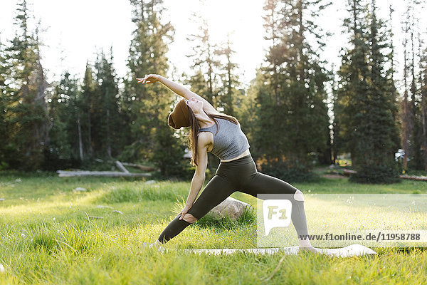 Woman practicing yoga in forest