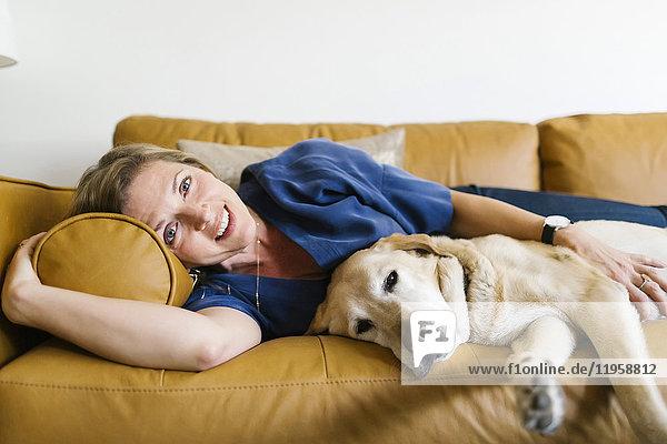 Woman and Labrador Retriever lying down on sofa