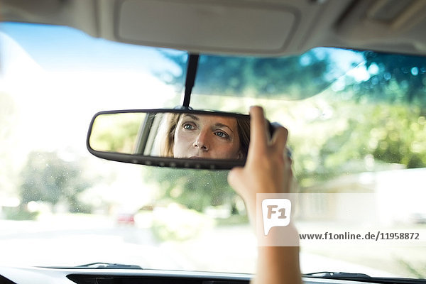 Woman adjusting rear-view mirror in car