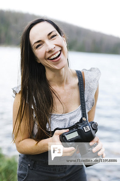 Portrait of woman holding camera by lake