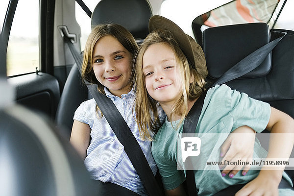 Brother (6-7) and sister ( 8-9) sitting in car