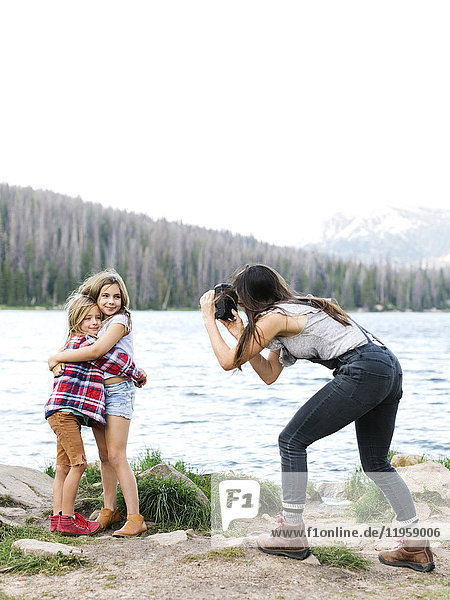 Mother photographing girl (8-9) and boy (6-7) by lake
