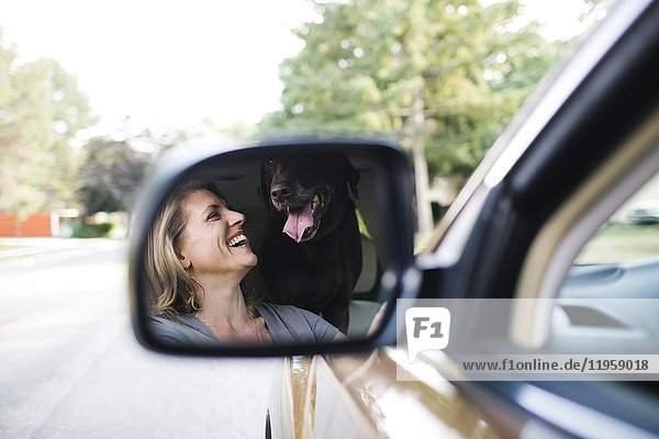 Woman and Labrador Retriever reflecting in side-view mirror