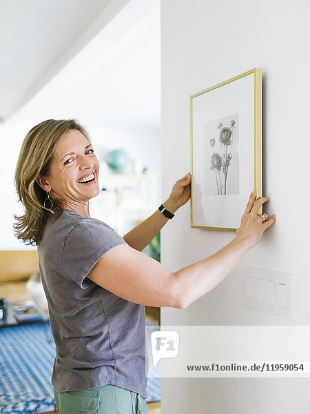 Smiling woman hanging picture frame on wall