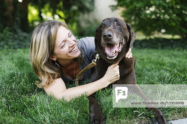 Smiling woman lying on grass with Labrador Retriever
