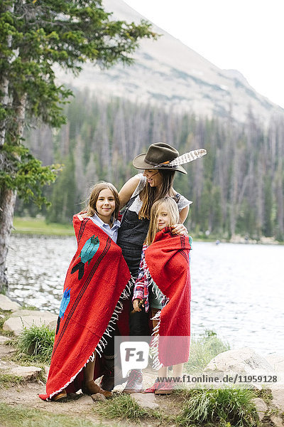 Mother with kids (6-7  8-9) wrapped in blanket standing by lake
