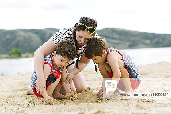 Mother playing with sons (4-5  6-7) on beach by lake