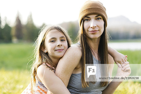 Portrait of mother and daughter (8-9) in meadow