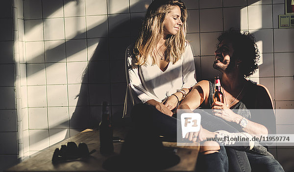 Man with brown hair holding beer bottle and a woman with long blond hair sitting indoors,  looking at each other,  smiling.