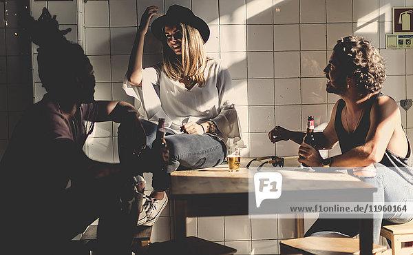 Zwei Männer und eine Frau sitzen drinnen um einen Tisch herum  halten Bierflaschen in der Hand und lächeln sich an.