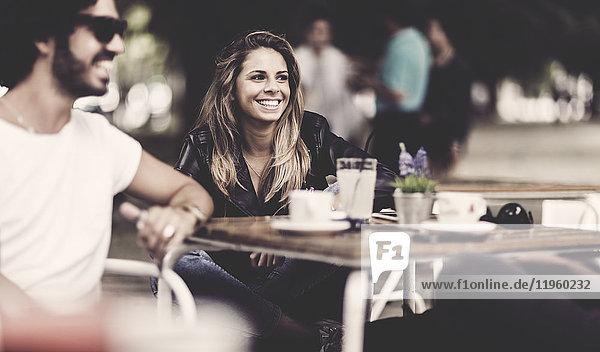 Bärtiger Mann mit Sonnenbrille und Frau mit langen blonden Haaren sitzt lächelnd draußen an einem Tisch in einem Cafe.