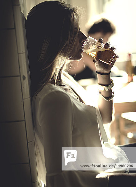 Side view of woman with long blond hair standing indoors  drinking beer from a glass.