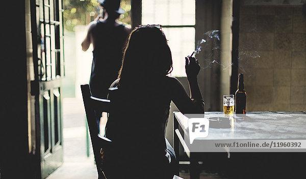 Rückansicht der Silhouette einer Frau  die drinnen an einem Tisch sitzt und Zigarette  Bierglas und Flasche auf dem Tisch raucht.
