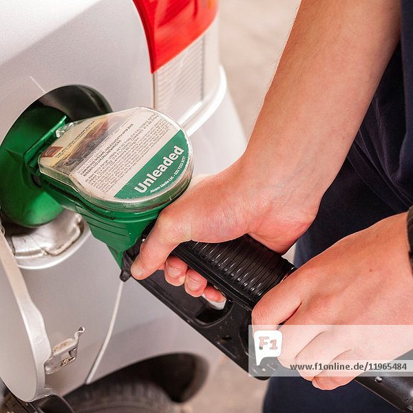 A man filling his car up with unleaded petrol in the Uk.