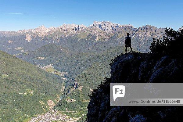 Europe  Italy  Veneto  Agordino  Dolomites  mountaineer silhouette towards the village of Cencenighe Agordino and the Biois valley.
