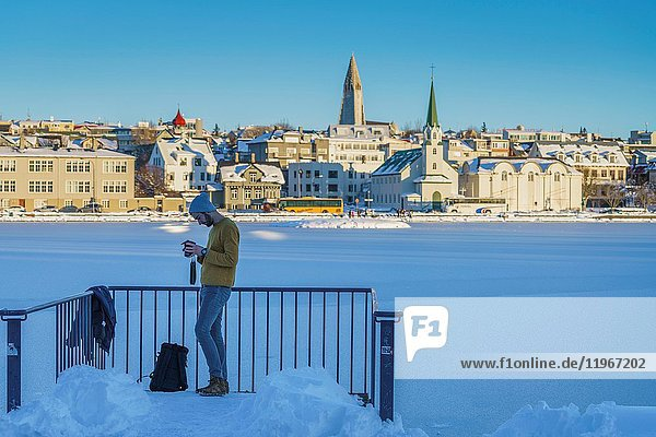 Man looking at his camera at the frozen pond in Reykjavik  Iceland.