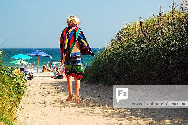 A young man arrives at Ditch Plains Beach,  Montauk Long Island for summer fun