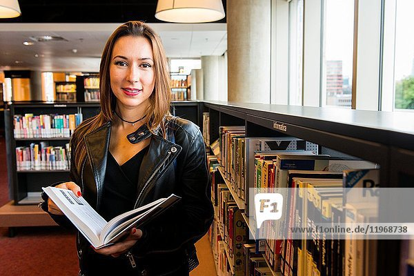 Rotterdam  Netherlands. Young  brunette and caucasian immigrant woman from the Ukraine  visiting the Public Library to read and learn the Dutch language.