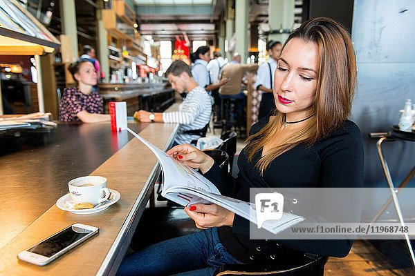 Rotterdam  Netherlands. Portrait young adult brunette woman sitting at a cafe's reading and newspaper table with a cup of coffee and a magazine.