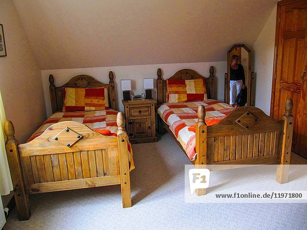 Mirrow with young woman in bedroom of B&B in Portree  Skye island  Inner Hebrides  Scotland  UK.