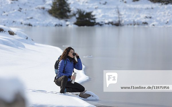 A view of a winter trekking where the woman sits by the lake and drink a cup of tea  Colbricon Lake  Trento province  Trentino Alto Adige  Italy  Europe.