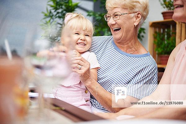 Ältere Frau lacht mit Kleinkind-Enkelin beim Familienessen auf der Terrasse