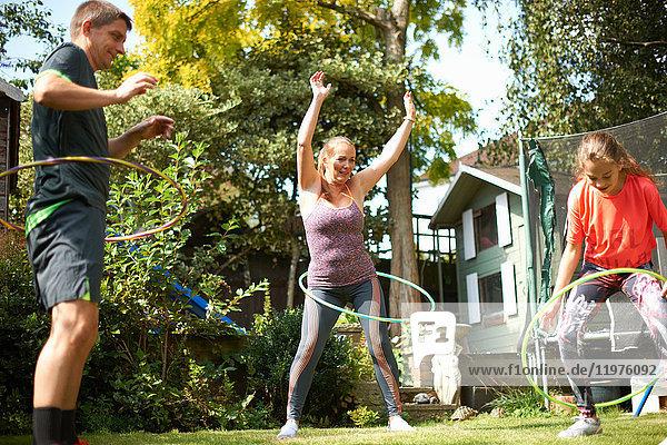Reifes Paar und jugendliche Tochter beim Hula-Hoop-Reifen im Garten