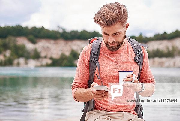 Mann hält Emaillebecher mit Mobiltelefon  Krakau  Malopolskie  Polen  Europa