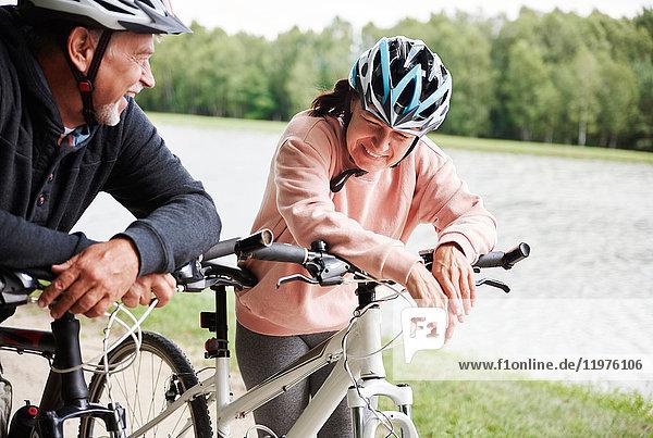 Ein reifes Ehepaar  das mit Fahrrädern auf dem Land unterwegs ist und lacht