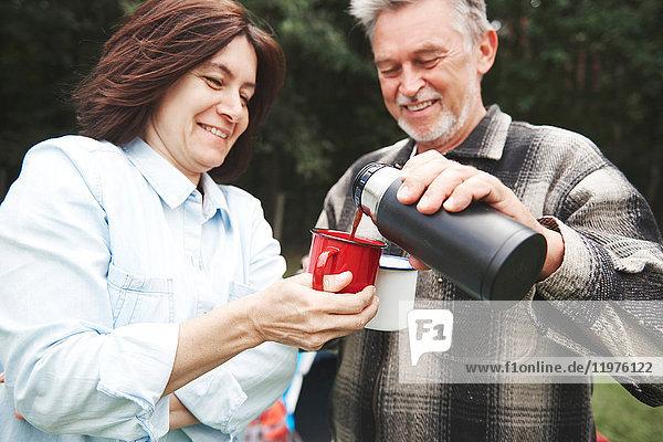 Reifes Paar im Freien  Mann gießt heißes Getränk aus Getränkeflasche
