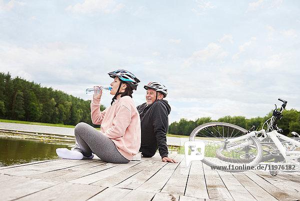 Ein erwachsenes Paar entspannt sich auf dem Steg  Fahrräder neben sich