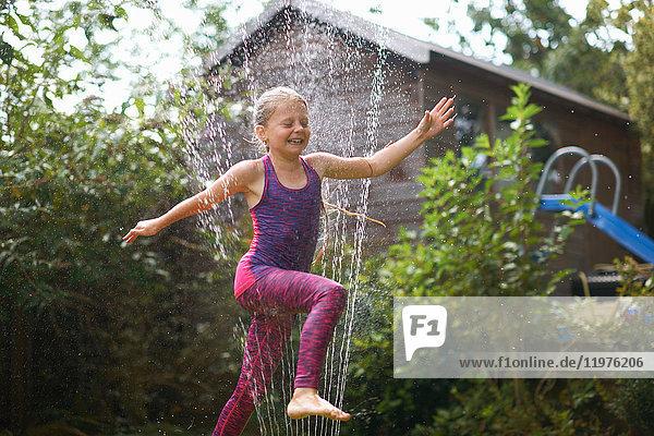 Mädchen springt über Gartensprenger