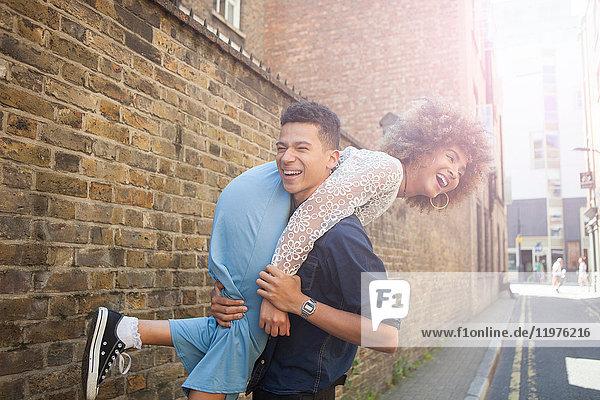 Junges Paar albert auf der Straße herum  Mann trägt Frau über die Schulter