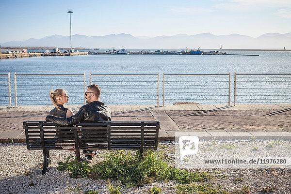 Rückansicht eines Paares von Angesicht zu Angesicht auf einer Parkbank,  Cagliari,  Sardinien,  Italien,  Europa