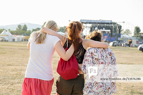 Three female friends at festival  rear view