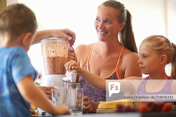 Reife Frau und Kinder mischen frischen Smoothie in der Küche