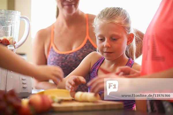 Mädchen und Familie bereiten Obst für Smoothie in der Küche zu